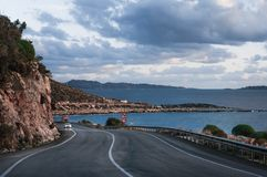 Asphalt road and car between mountainous area and seaside. Highway in mountains and sea. Travel background stock image