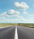 Asphalt road and clouds Stock Images