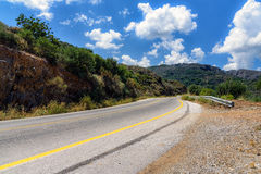Asphalt road and cloudy sky in mountains on Crete island Royalty Free Stock Photography