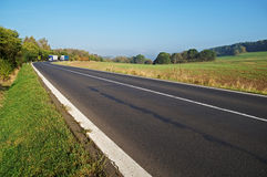 Asphalt road in the countryside, blue and white truck coming around in the distance the bend Stock Image