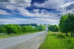 Asphalt road in the countryside through green summer fields stock photography