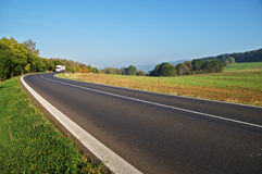 Asphalt road in the countryside, white truck coming around in the distance the bend Royalty Free Stock Image