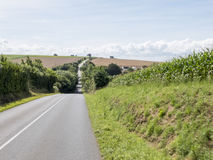 Asphalt road crossing the green hills of Brittany. Cultivated fields in the background, with homes and cloudy sky Royalty Free Stock Photography