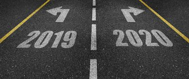 New year 2020 road marking. An asphalt road with a crossroad, the year 2019 going in one direction and the year 2020 going in the other one Stock Photography
