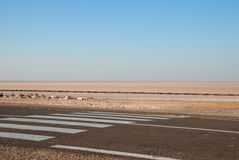 Asphalt road with crosswalk in desert. Asphalt road with crosswalk in Sahara Desert Royalty Free Stock Photos