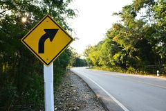 Asphalt road with curve traffic sign. In forest Stock Photo