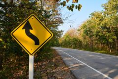 Asphalt road with curve traffic sign. In forest Royalty Free Stock Image