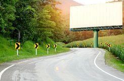 Asphalt road curved side of a cornfield with arrow signs,Big white billboard on the curve. stock photos