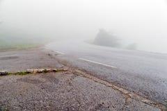 The asphalt road in dense fog. Dense fog over the damp road in cloudy summer day Stock Image