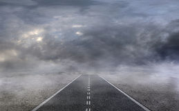 Asphalt road in a desert with dark cloudy sky. On the background Stock Images