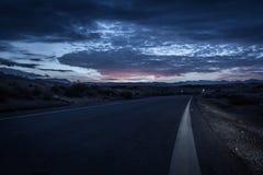 Asphalt road. In the desert at dusk Royalty Free Stock Image
