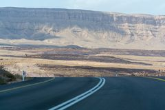 Asphalt road in desert Negev, Israel, road 40, transport infrast. Ructure in desert, scenic mountains route in Mizpe Ramon canyon in Israel Royalty Free Stock Photo