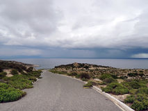 Asphalt road through deserted area leading to stormy sea. Dark, gloomy day. Asphalt road passing through deserted area with thorn-bushes and rocks. Sea seen in Stock Photos