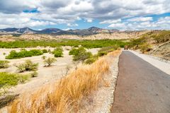 Asphalt road from Dili to Baucau with an truck in a distance. Dry savanna. Rural landscape, nature of East Timor or Timor-Leste. Asphalt road from Dili to royalty free stock image
