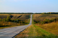 Asphalt road disappearing into horizon on background of meadows forests and blue sky Stock Photo