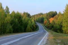 Asphalt road disappearing into horizon on background of meadows forests and blue sky Royalty Free Stock Photography