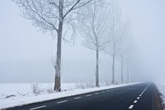 Asphalt road disappearing in winter haze Stock Photography