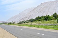 Asphalt road on the edge of the dumps of the mines of Belarus, the city of Soligorsk.  Royalty Free Stock Photos