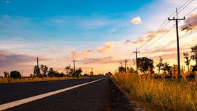 Asphalt road with electric pole and meadows along the way. Count Royalty Free Stock Photography
