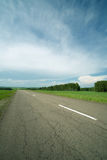 Asphalt road in field Royalty Free Stock Image