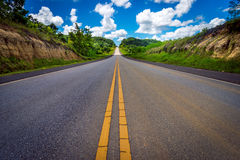 Asphalt road through the field and clouds on blue sky Stock Photo