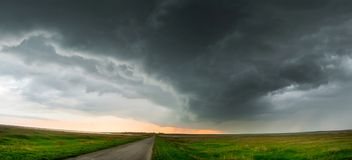 Asphalt road in a field with green grass under the sky with large dark storm clouds. In a wide format Stock Photography