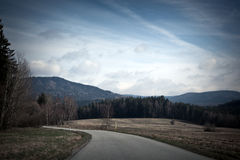 Asphalt road among fields, forests and mountains Stock Photography