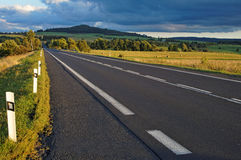 Asphalt road through the fields towards the horizon Royalty Free Stock Photography