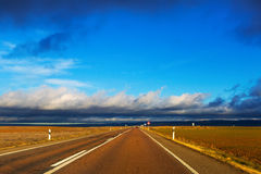 Asphalt road among fields Royalty Free Stock Photography