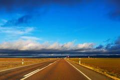 Asphalt road among fields Royalty Free Stock Photo