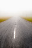 Asphalt road in fog Stock Images