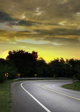 Asphalt road in forest with sunrise sky Royalty Free Stock Photos