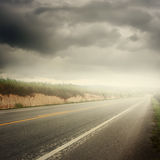 Asphalt road in forrest and rainclouds for transportation Royalty Free Stock Images