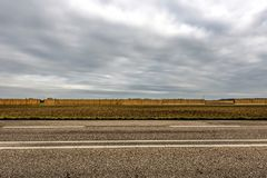 Asphalt road in front of a field with a long wall of hay piles Royalty Free Stock Photo