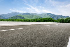 Asphalt road in front of the green mountain Royalty Free Stock Image