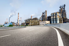 Asphalt road in front of the industrial building Stock Photography