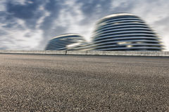 Asphalt road  and fuzzy modern buildings Royalty Free Stock Images