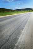Asphalt road goes into the distance and disappears into the woods Royalty Free Stock Photography