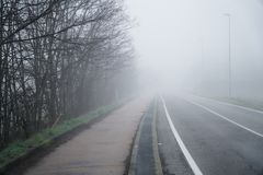 Asphalt road that goes through a misty foggy dark misterious pempty fields.  Royalty Free Stock Photo
