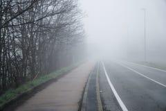 Asphalt road that goes through a misty foggy dark misterious pempty fields.  Stock Photo