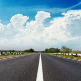 Asphalt road goes to horizon under clouds Stock Images