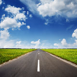 Asphalt road through the green field Royalty Free Stock Images