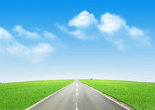 Asphalt road through the green field and blue sky Stock Photos