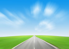Asphalt road through the green field and blue sky Royalty Free Stock Images