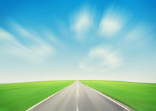 Asphalt road through the green field and blue sky Stock Images