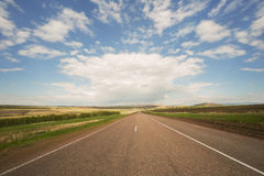 Asphalt road. Through the green field and clouds on blue sky in summer day stock photography