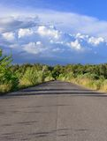 Asphalt road through green field and clouds on blue sky Royalty Free Stock Images
