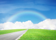 Asphalt road through the green field and sky with clouds and rai Royalty Free Stock Photos