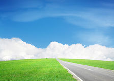 Asphalt road through the green field and sky with clouds Stock Photography