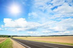 Asphalt road in green meadow Royalty Free Stock Photos